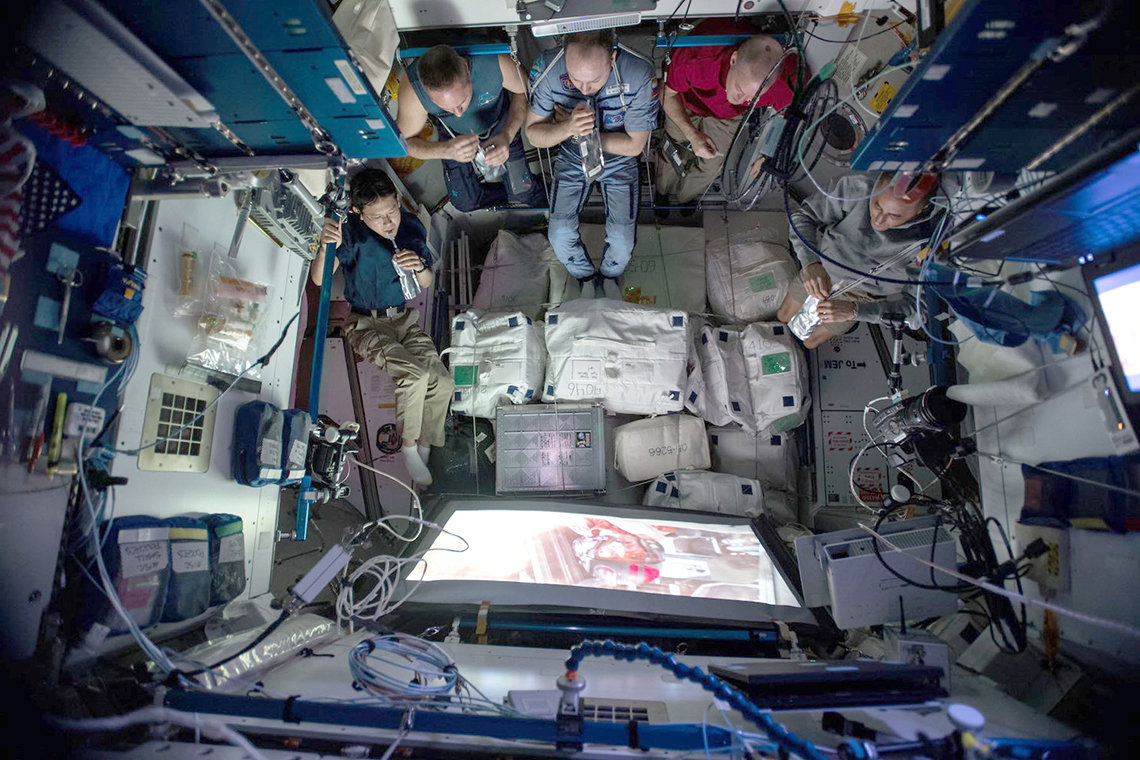 Overhead view of astronauts watching a movie aboard the ISS