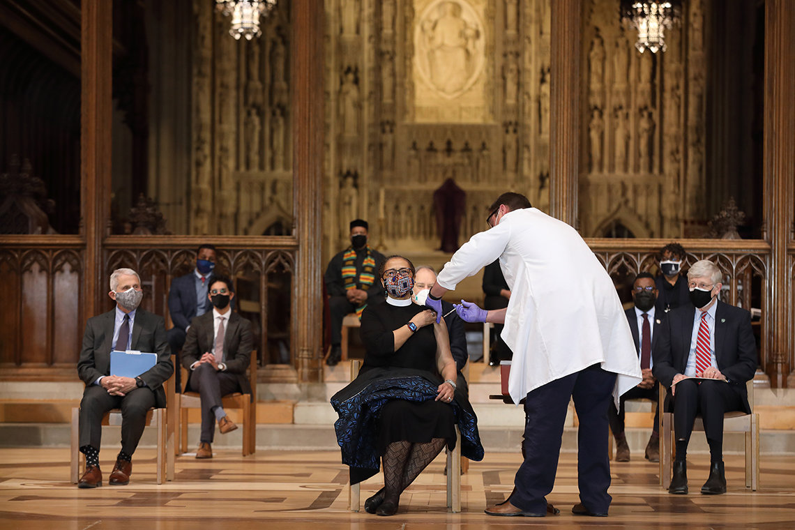 On the Cathedral stage, a seated nun receives an injection from a health worker in a lab coat.