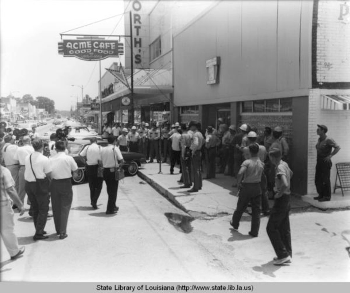 Black and white image of street corner where a group of people including police and photographers gather at a storefront.