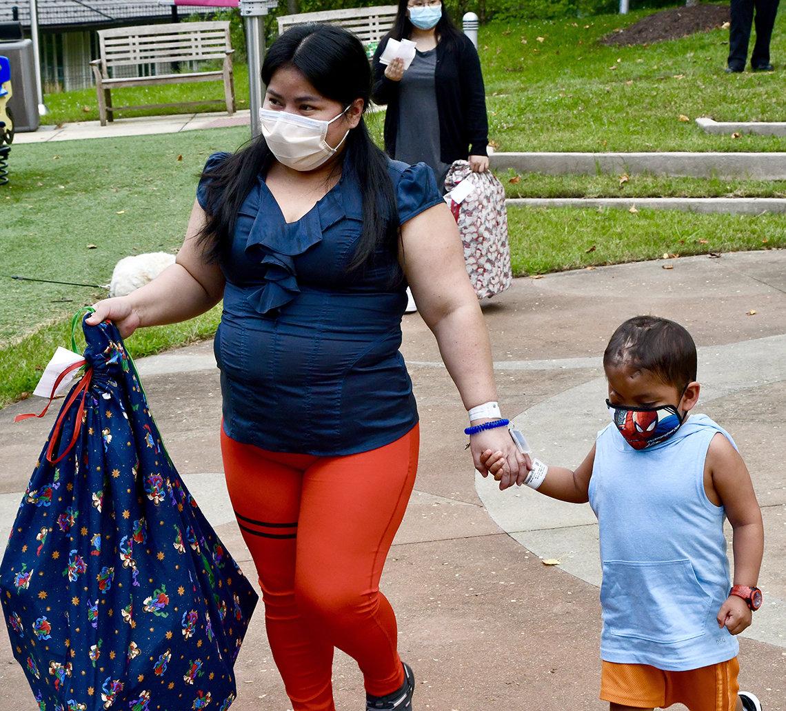 A woman holds a little boy's hand.