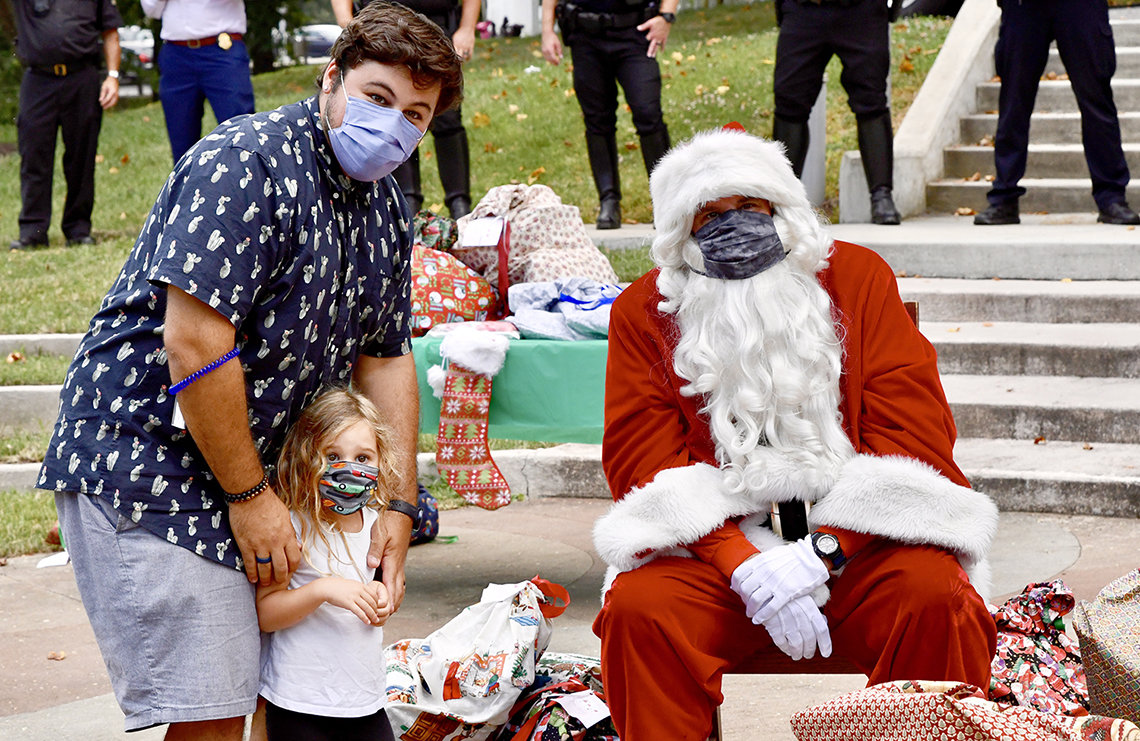 A man and his daughter stand next to seated, masked Santa.