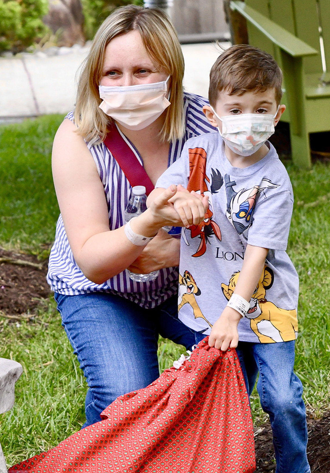 A woman stoops next to a little boy and holds his hand while he holds a bag.