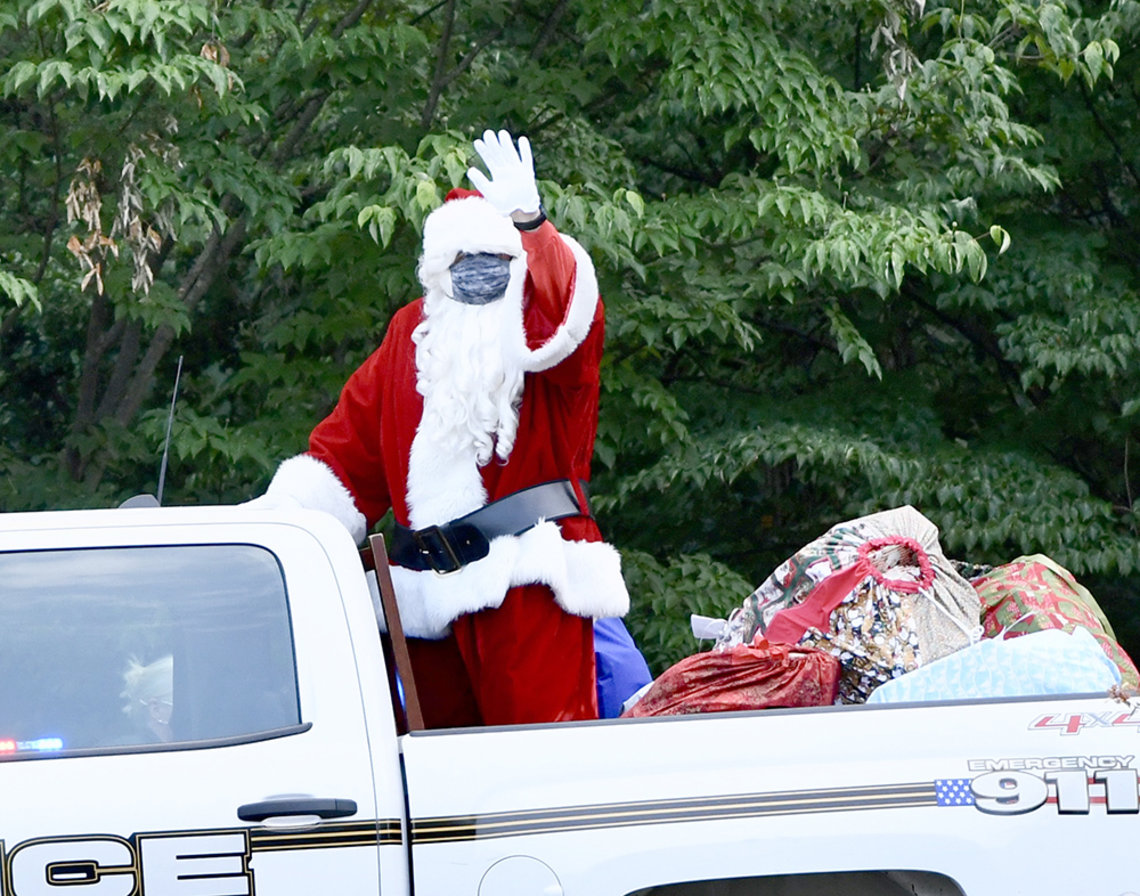 Santa waves from the bed of a pickup truck