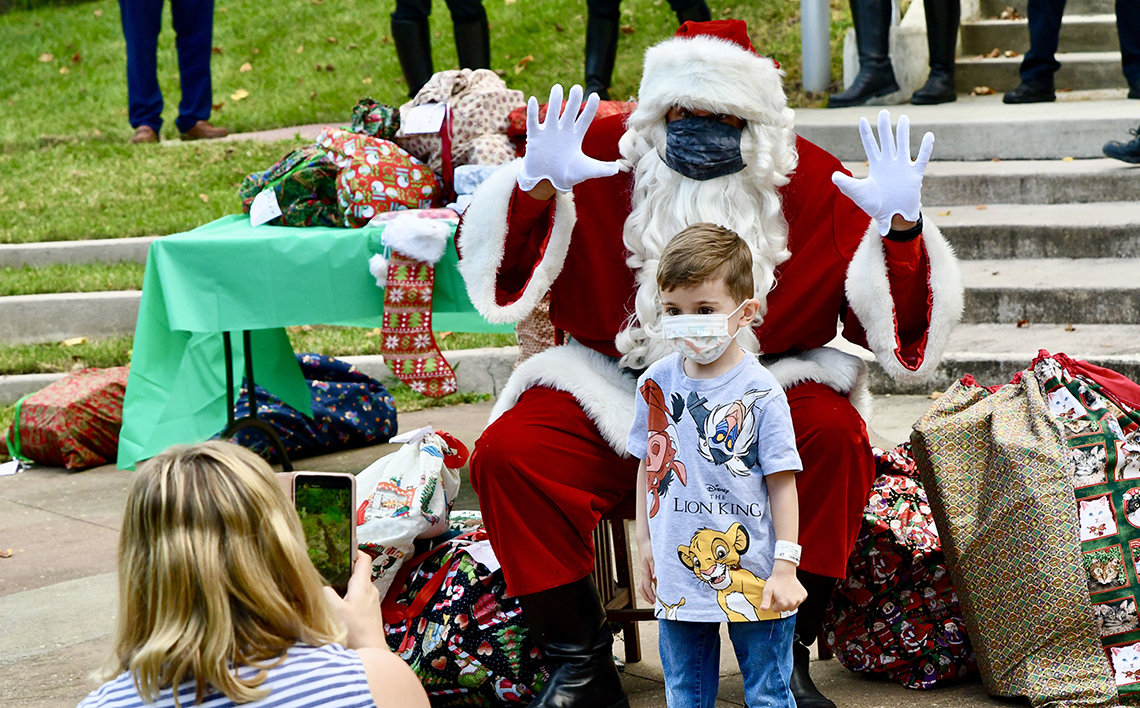 A little boy stands in front of masked Santa, who is holding his hands up with open palms