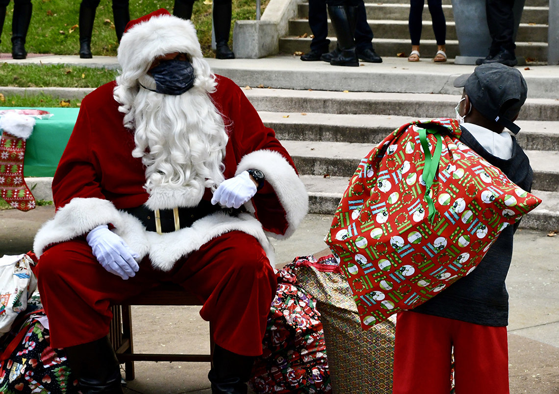 A little boy walks over to a seated Santa