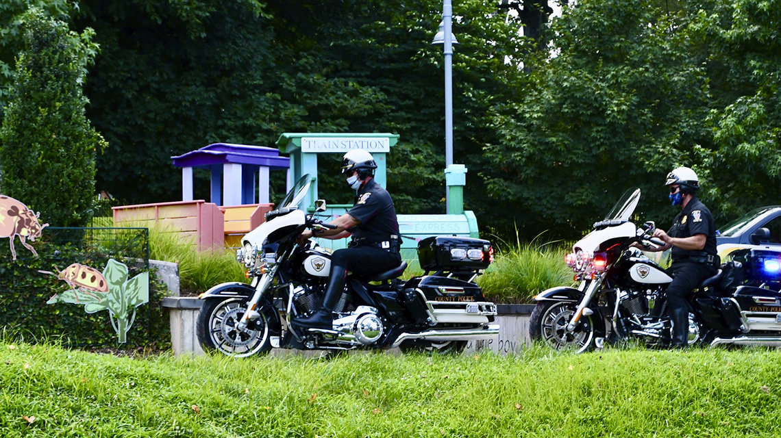 Two police officers riding motorcycles drive up to the inn.