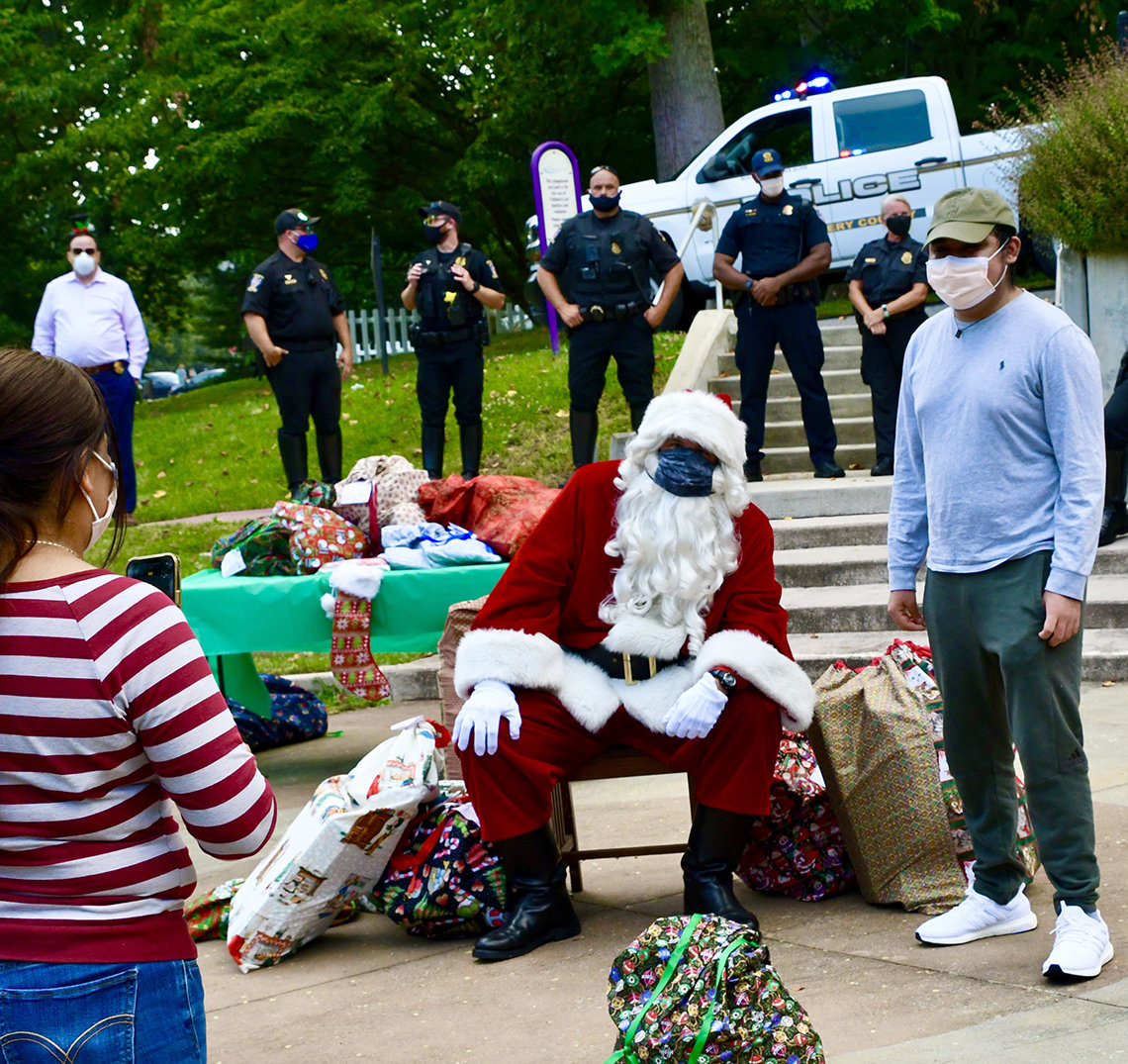 A woman takes a photo with her iphone of a young man wearing a blue longsleeve shirt and Santa.