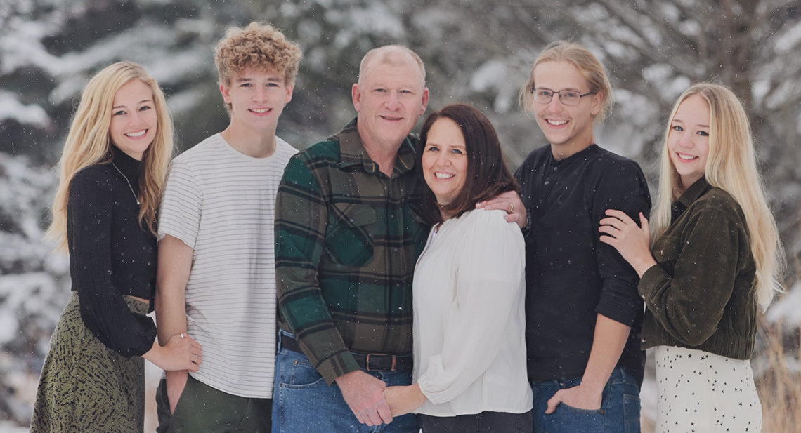 A wintertime photo of the Schmaedeke family, posing outside, surrounded by snow flurries