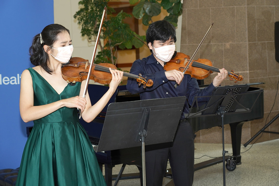 Two young adults play violins while masked in the atrium of the CC