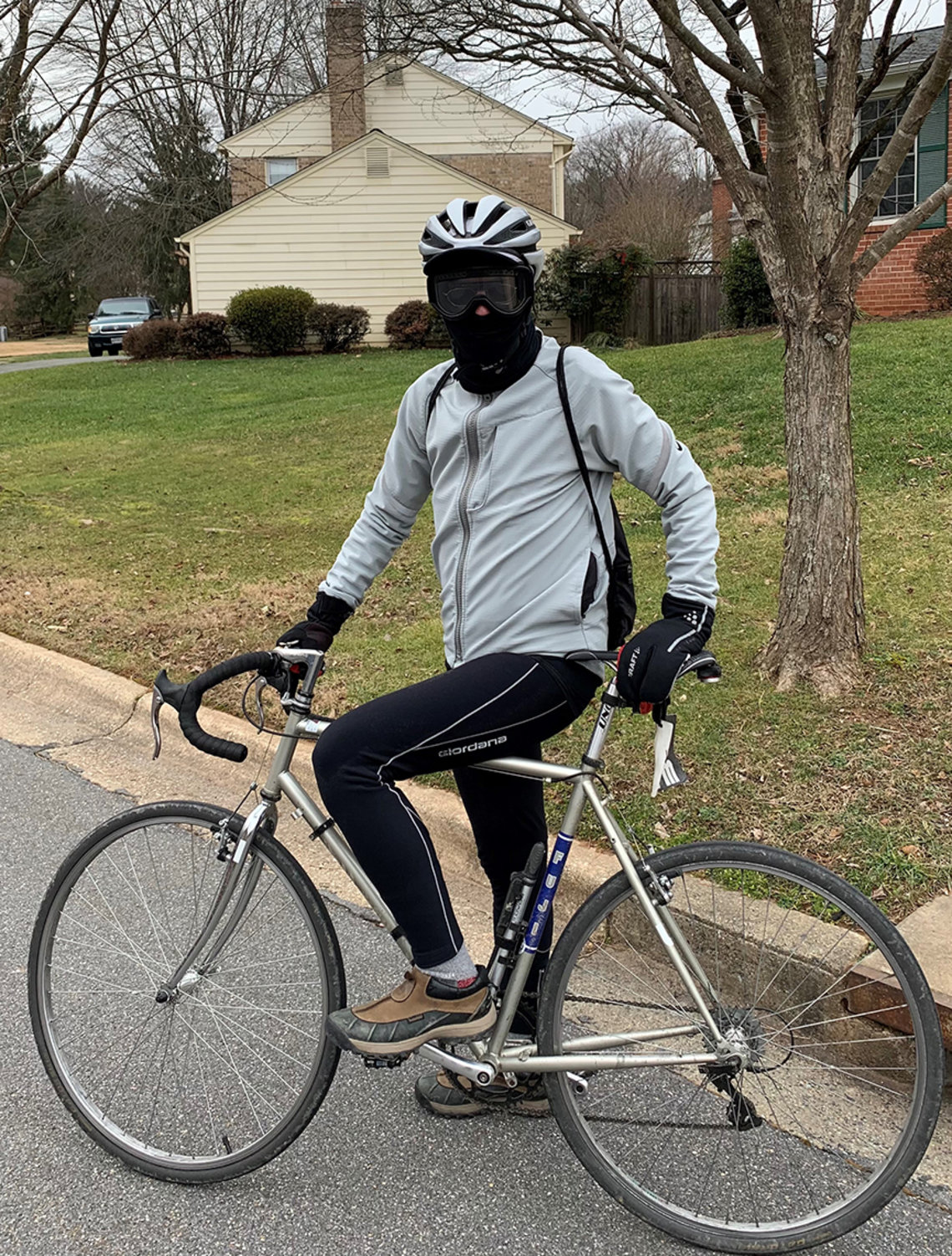 Murphy, dressed in warm clothes and a balaklava, sits on his bicycle outside his home.