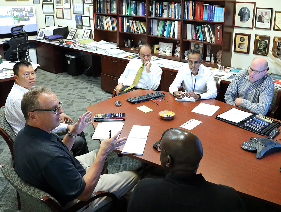 McManus sits at a conference table with several others
