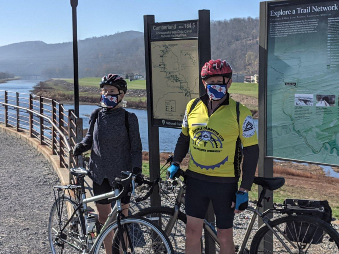Breen and her husband, with their bikes, stand in front of C&O Canal and posted trail maps.