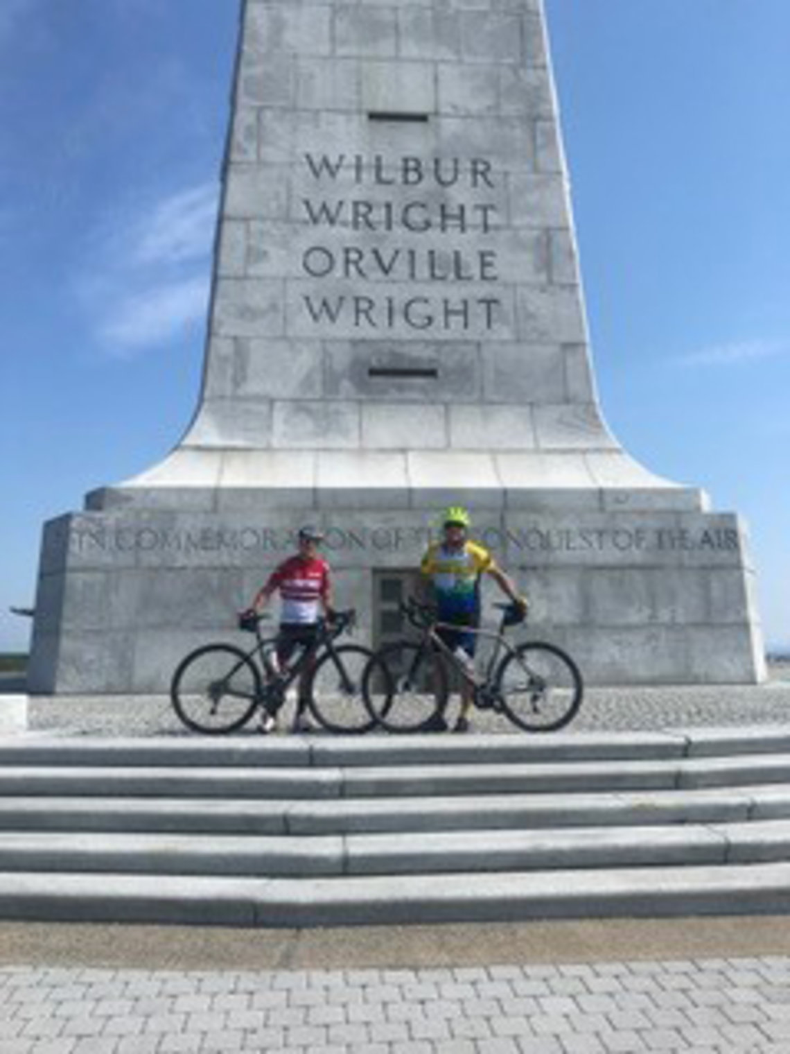 Steve Friedman and friend stand with their bicycles on steps of Wright Brothers Memorial.