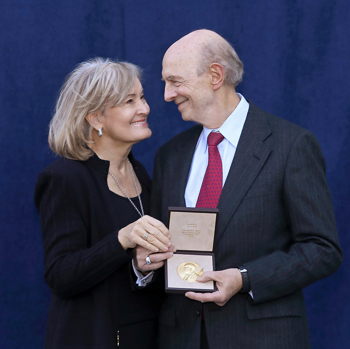 Alter and his wife look at medal.