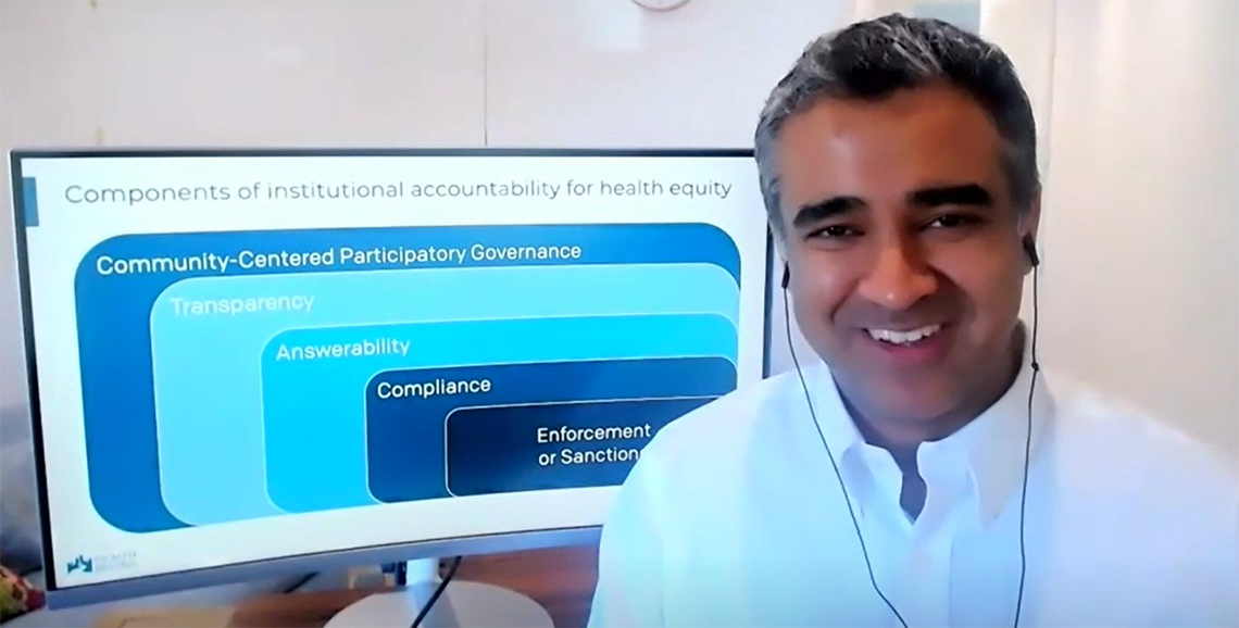 A smiling Manchanda sits in front of a monitor with a slide: Components of institutional accountability for health equity