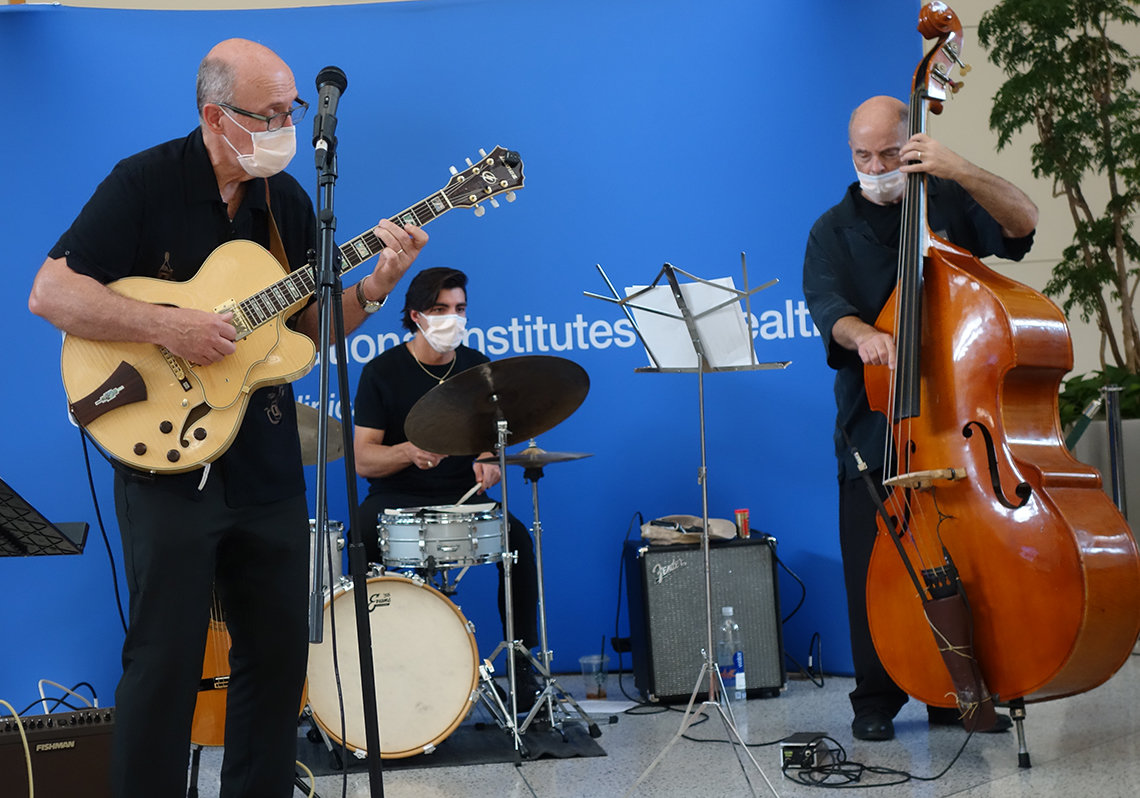 Three men in the CC atrium, playing guitar, drums and bass