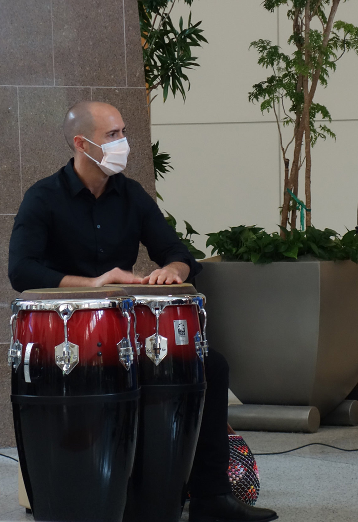 A man rests his hands on conga drums.