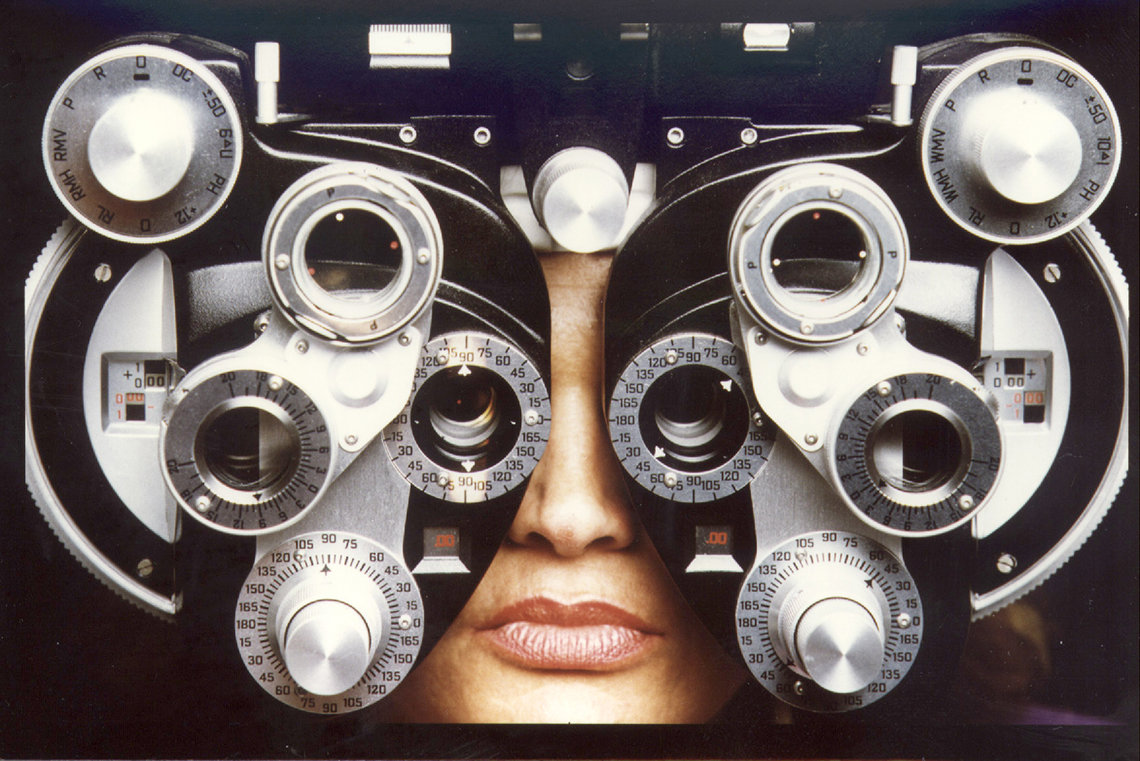 Huss' face sits behind a phoropter, an instrument commonly used by eye care professionals during an eye examination, and contains different lenses used for refraction of the eye during sight testing.