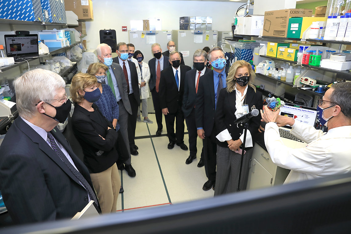A group of masked Senators form a semi-circle around Mascola, who is holding up a 3-d printing of SARS-Cov-2 virus particle.