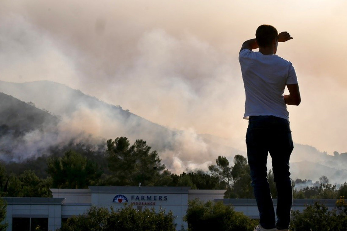 A man looks towards a mountain covered in heavy wildfire smoke