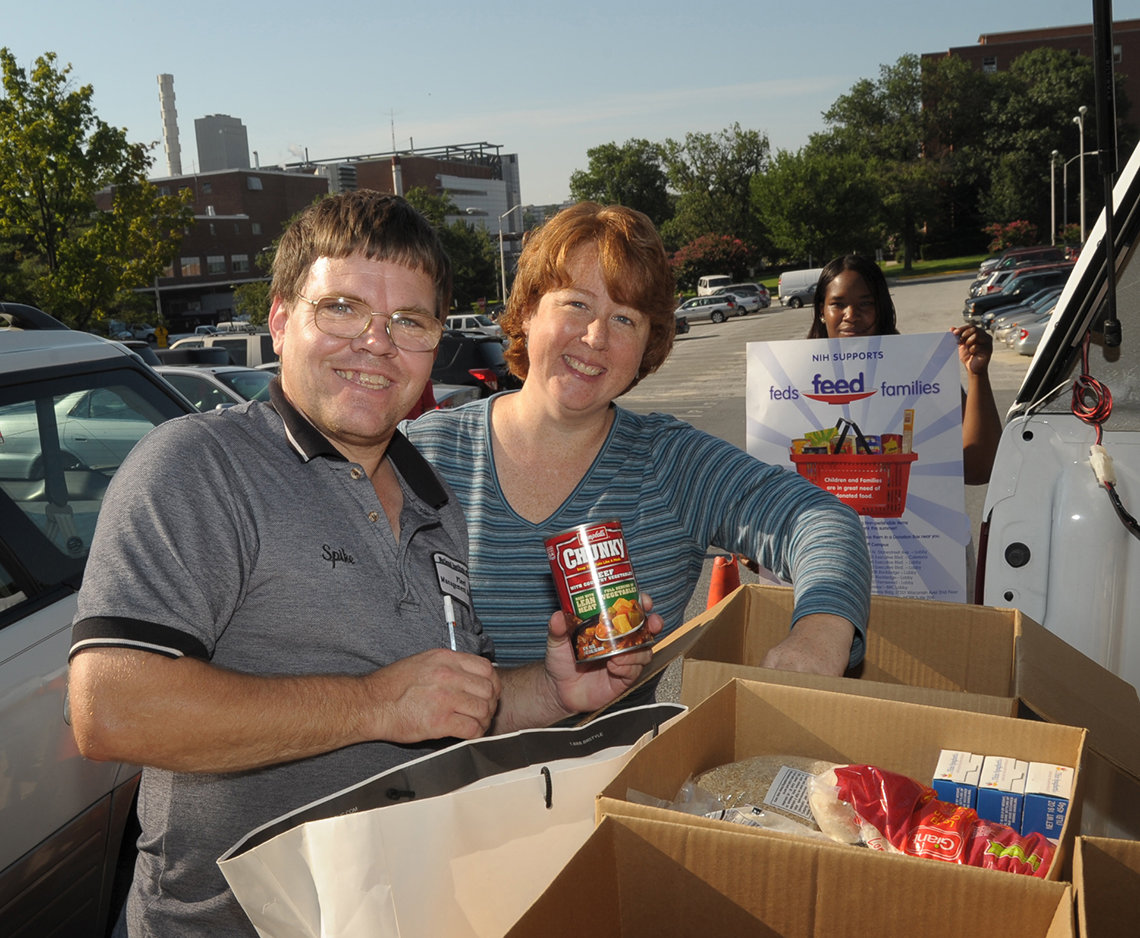 A man holds a can of Chunky Beef soup while a woman puts an object in a cardboard box full of nonperishable food.