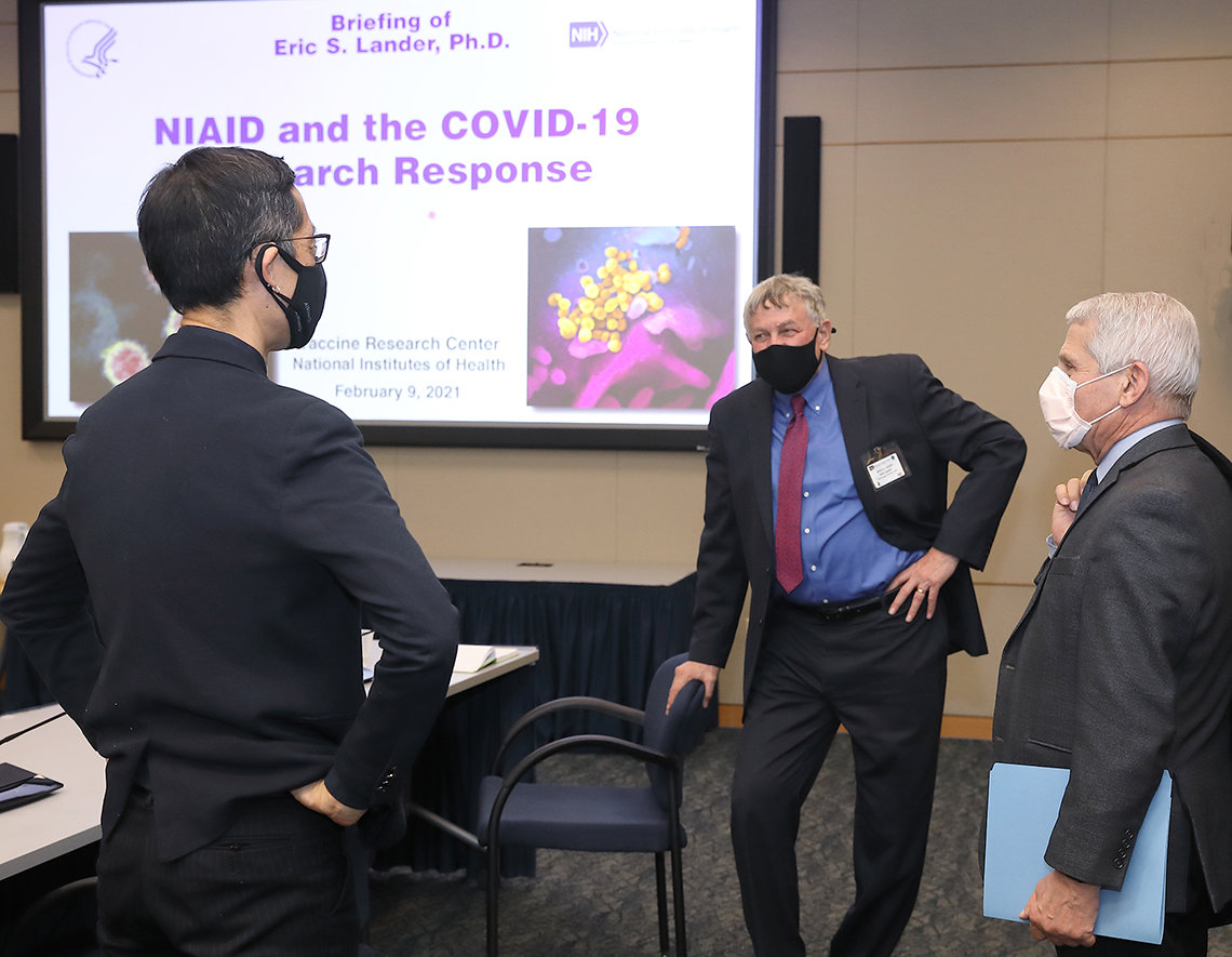 """Koizumi, Lander and Fauci stand talking in front of video screen with purple slide, """"NIAID and the COVID -19 Research Response"""""""