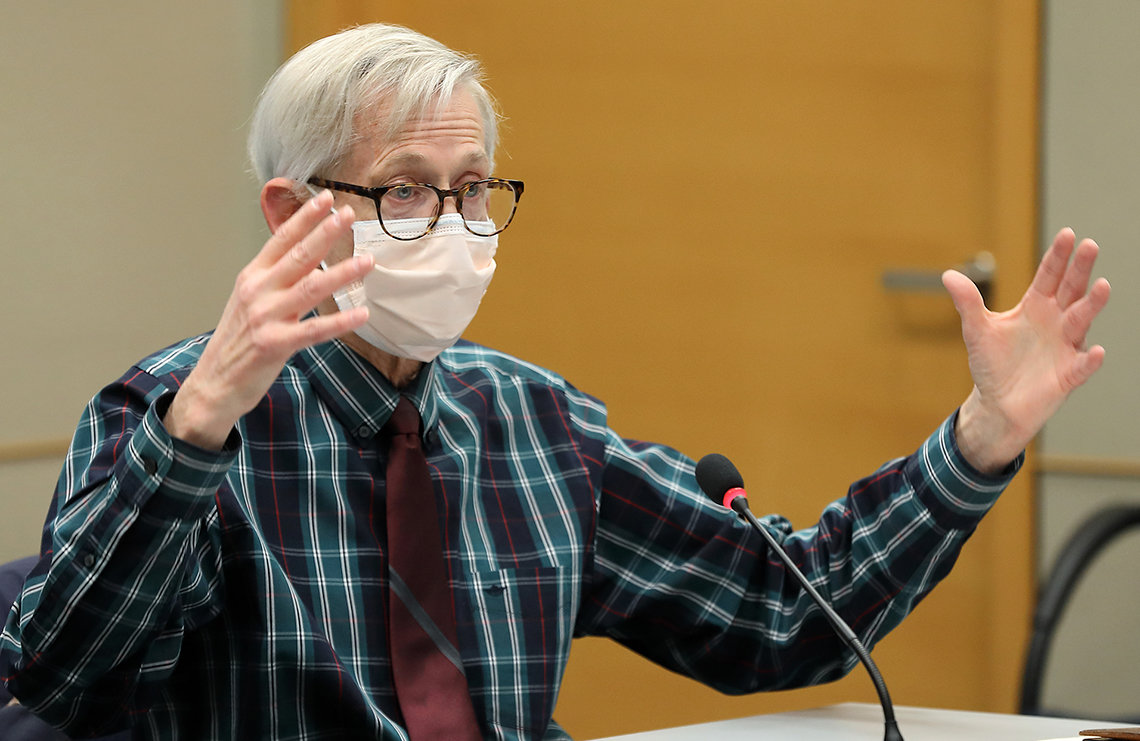 Lane in blue shirt and white mask with hands extended as he speaks