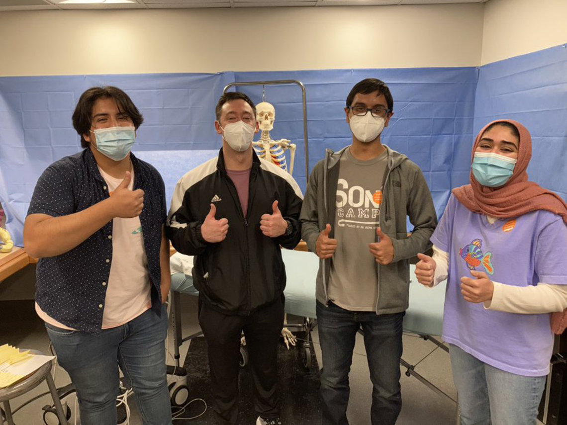 Four masked students gives a thumb up hand gesture. Behind them is a model skeleton.