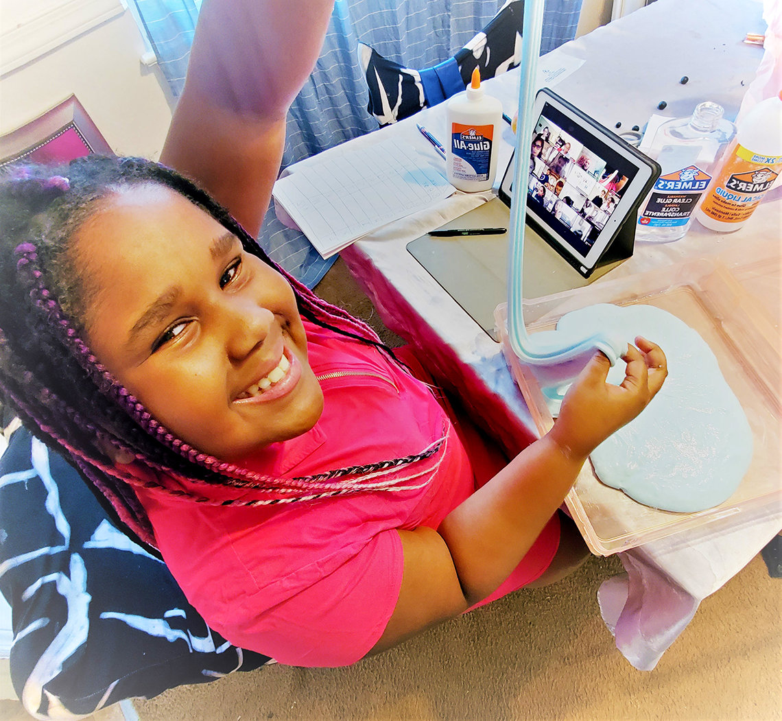 Kennedy smiles as she holds up a science project she made--slime, a mixture between a solid and a liquid.