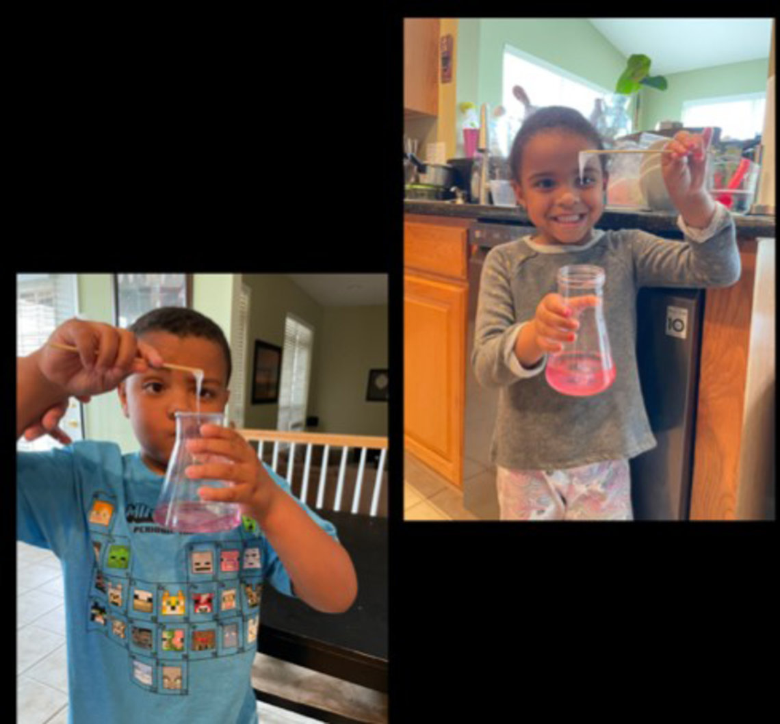 Isaac and Gabriella hold up a beaker with strawberry DNA