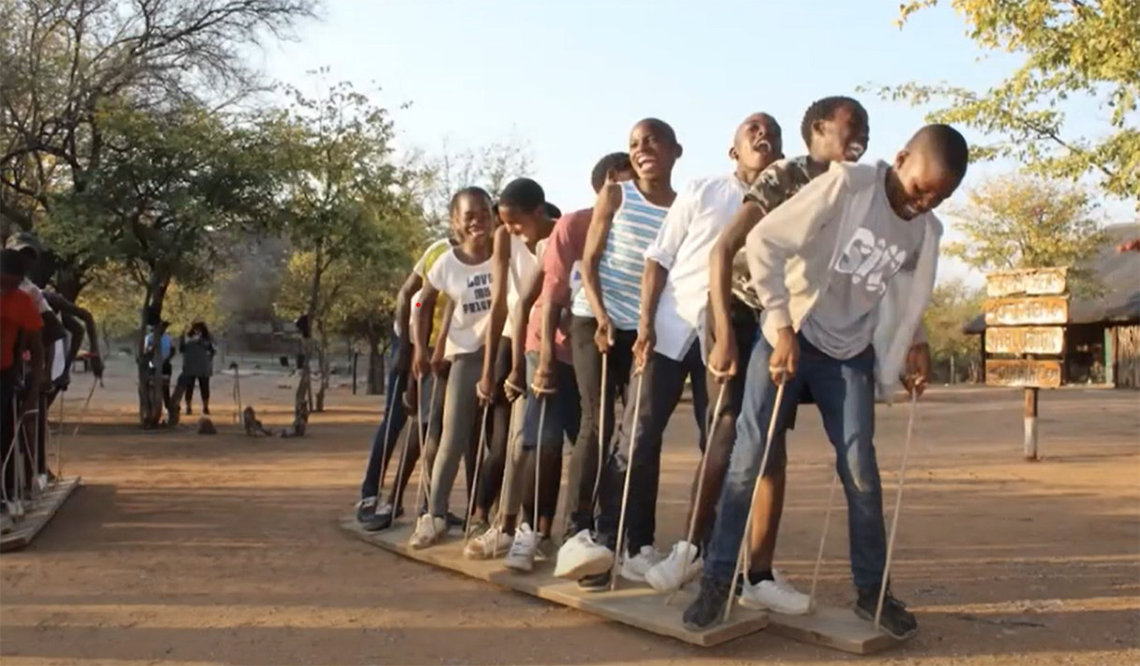 Children laugh while helping each other balance on a long board during a team exercise in Botswana in Africa.
