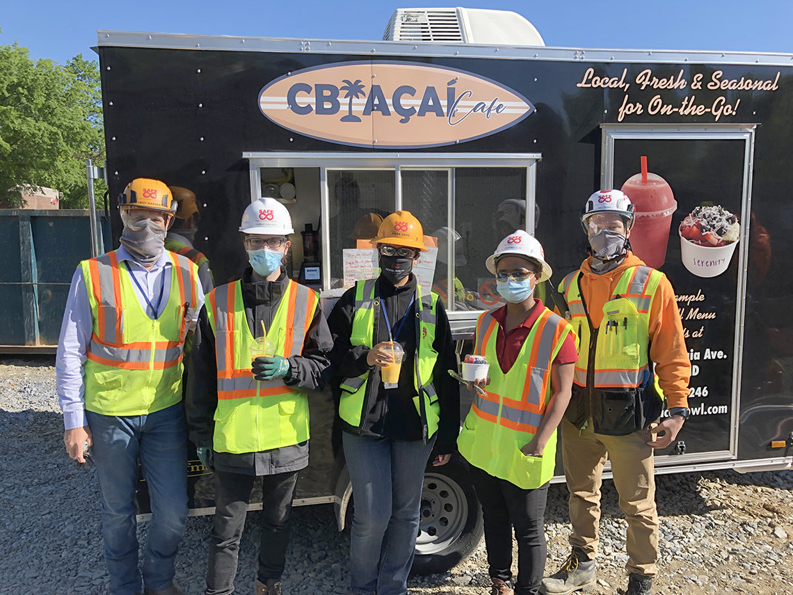Construction workers in safety helmets and vests smile in front a food truck.
