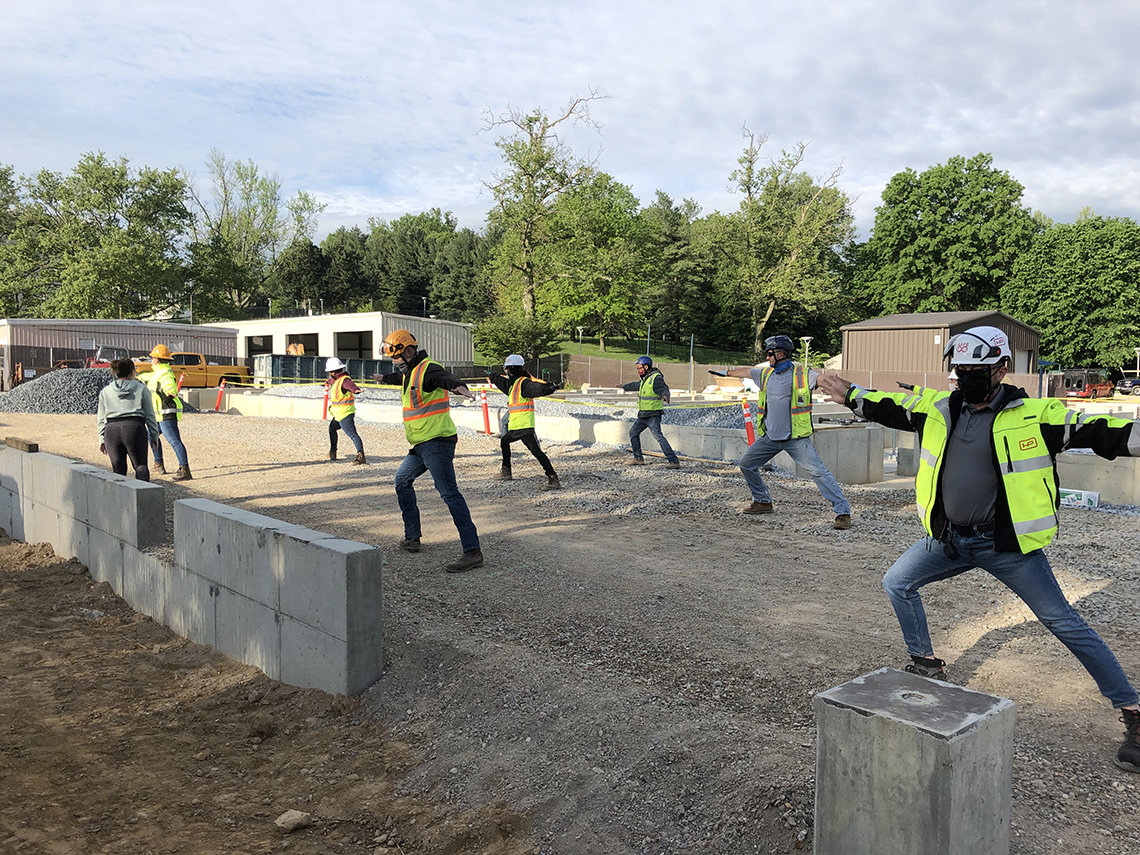 Instructor gesturing toward group of construction crew members who are posing with arms outstretched.