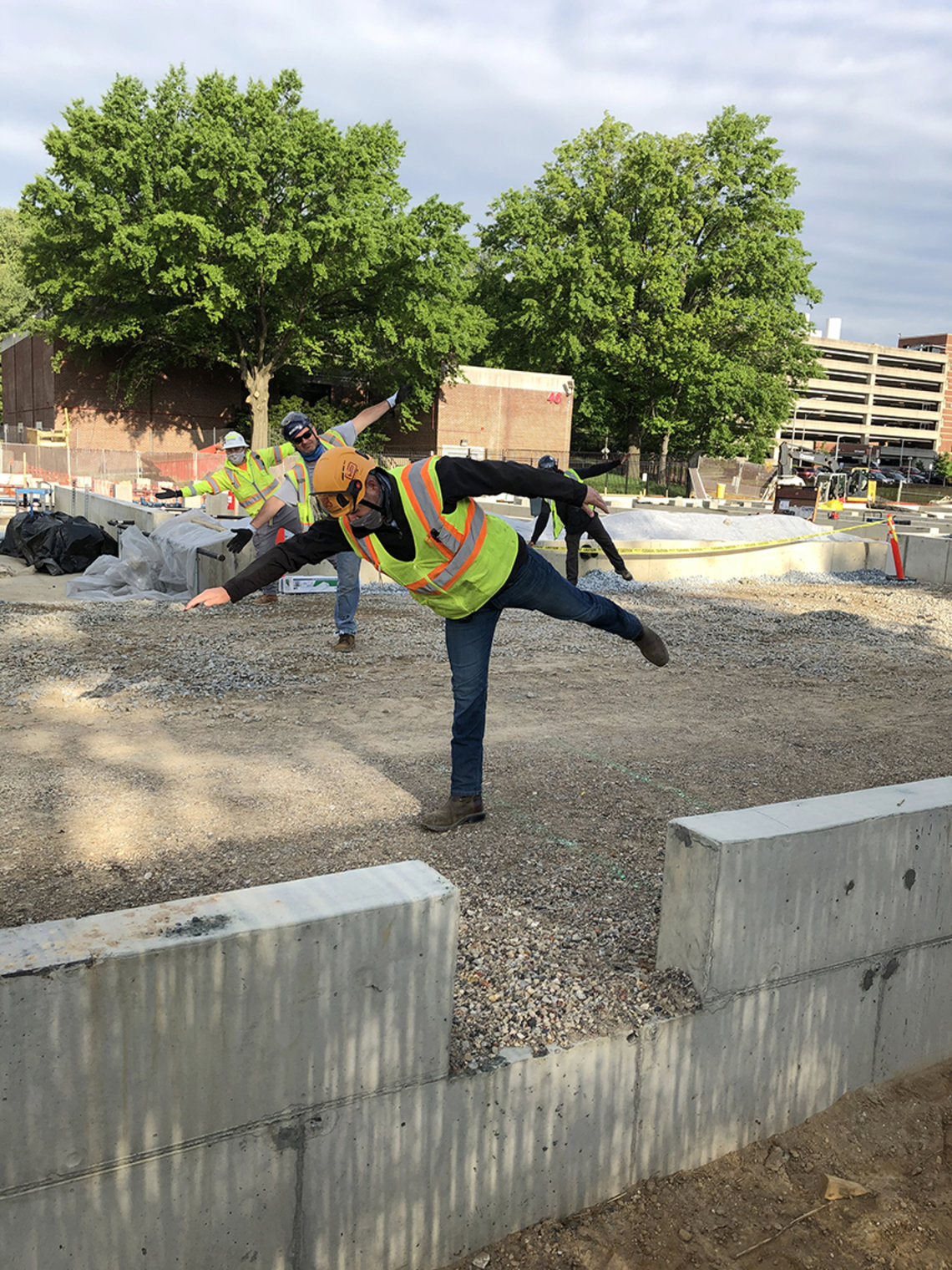 Close up view of individual construction worker standing on one leg with the other leg and one arm stretched out.
