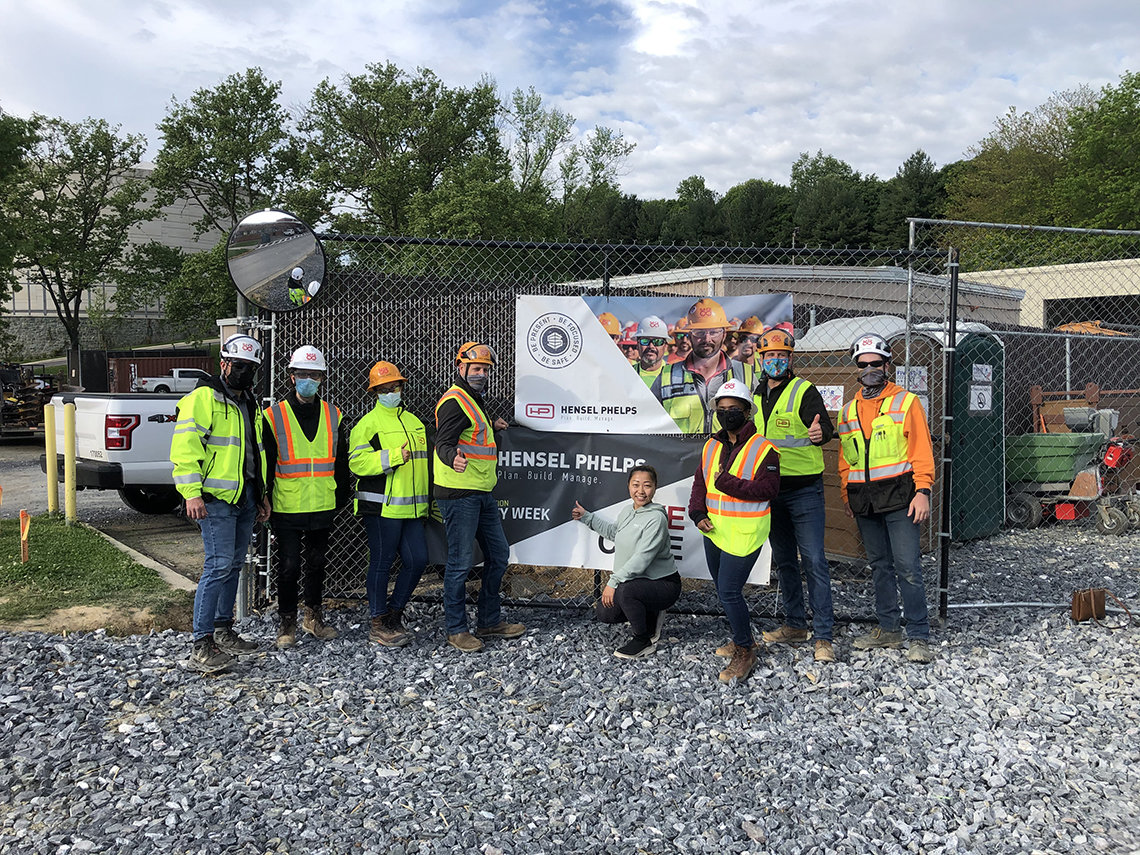Several construction workers in safety helmets and vests pose at job site with a yoga instructor in front of company sign.