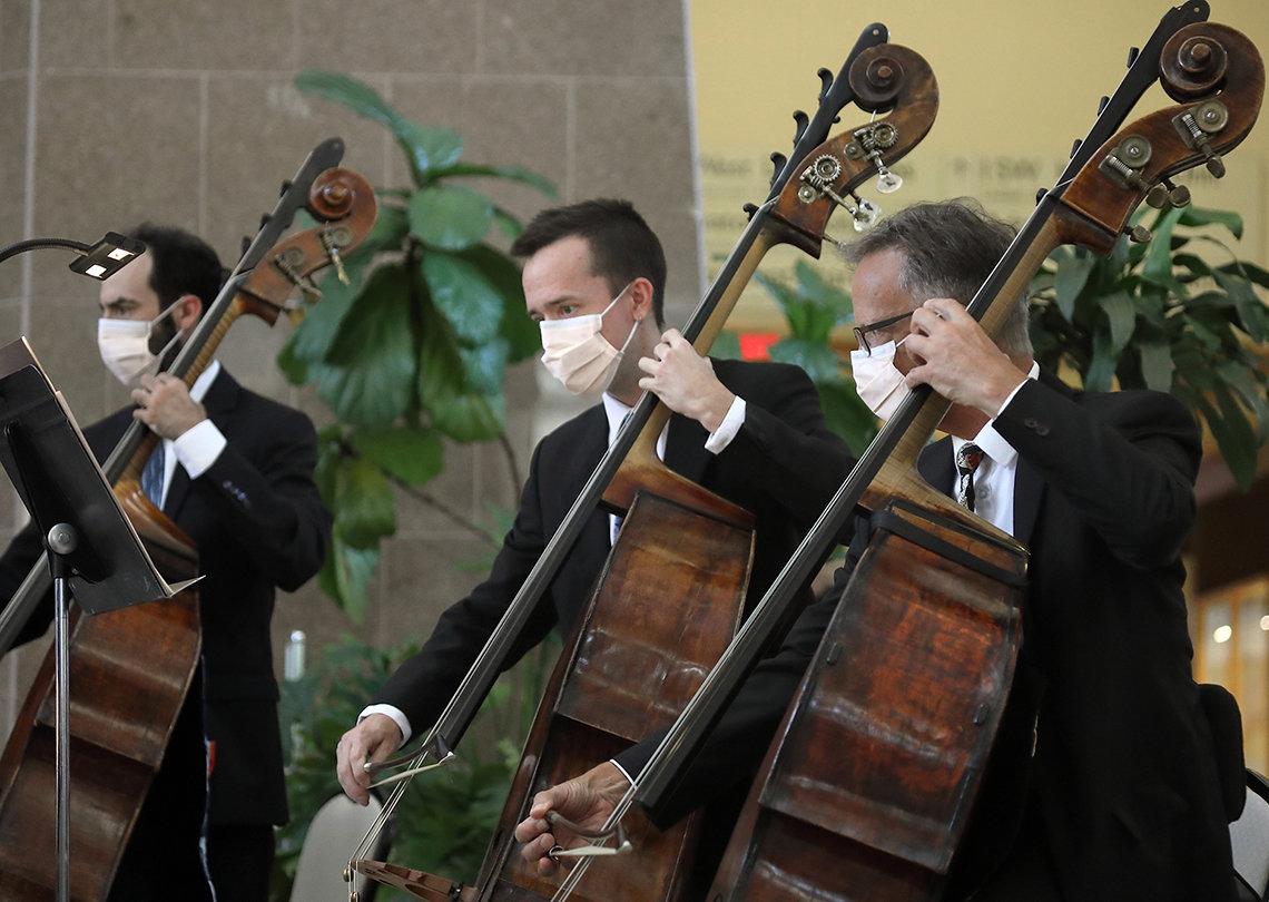 Three men wearing masks glide their bows across their cellos.