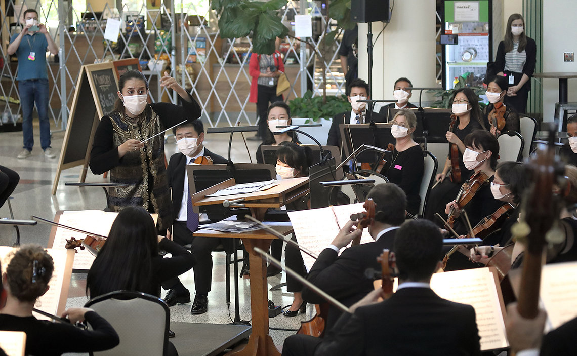 Members of the orchestra, all in masks with their string instruments and sheet music, follow the conductor as several staff members and a doctor in blue scrubs look on.