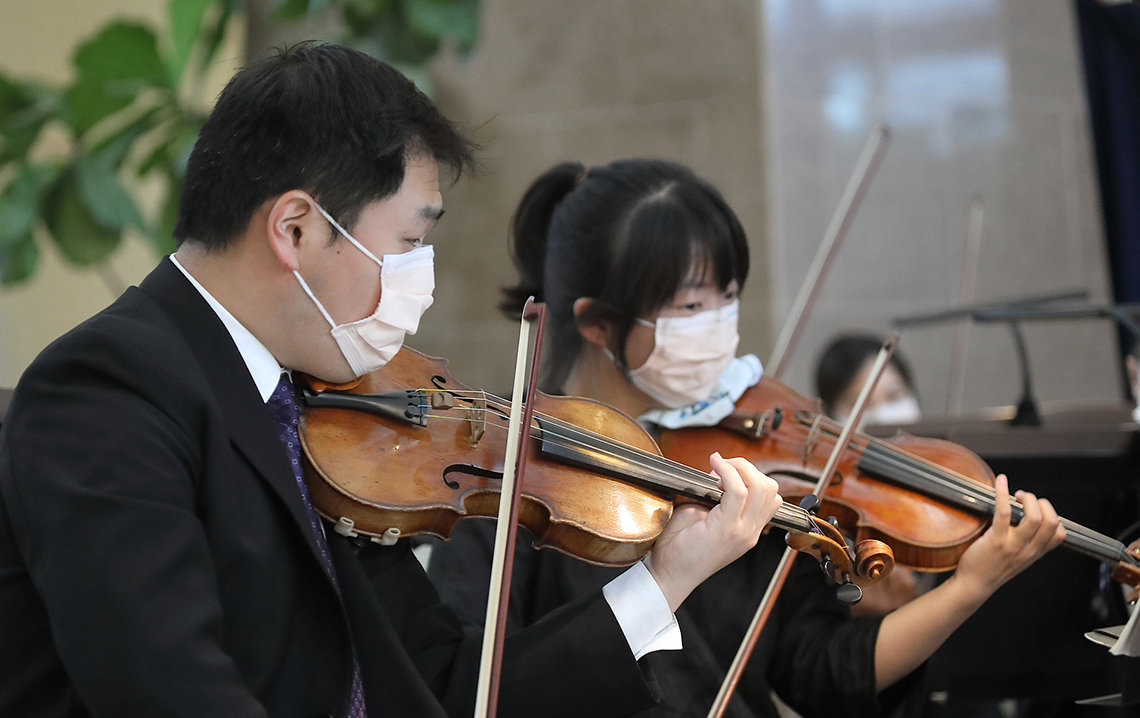 Two Asian musicians, wearing masks, hold their bows up to their violins in the atrium.