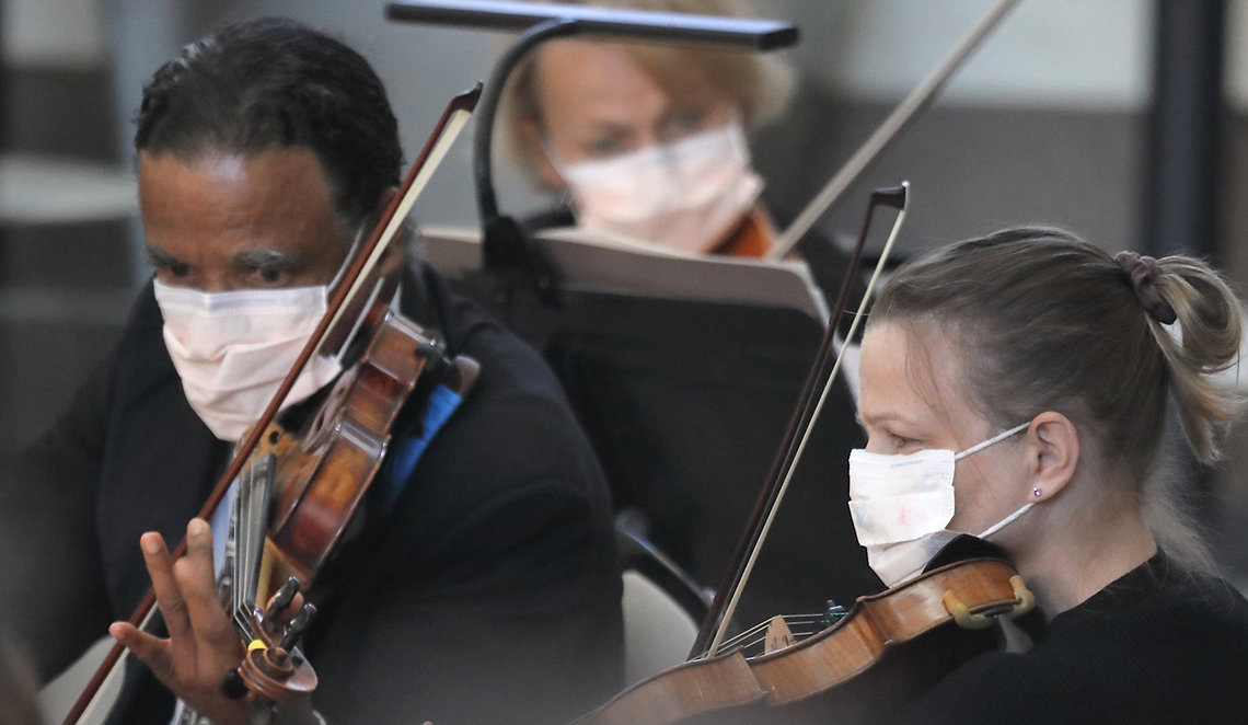 Three masked musicians look toward music stands playing their violins.
