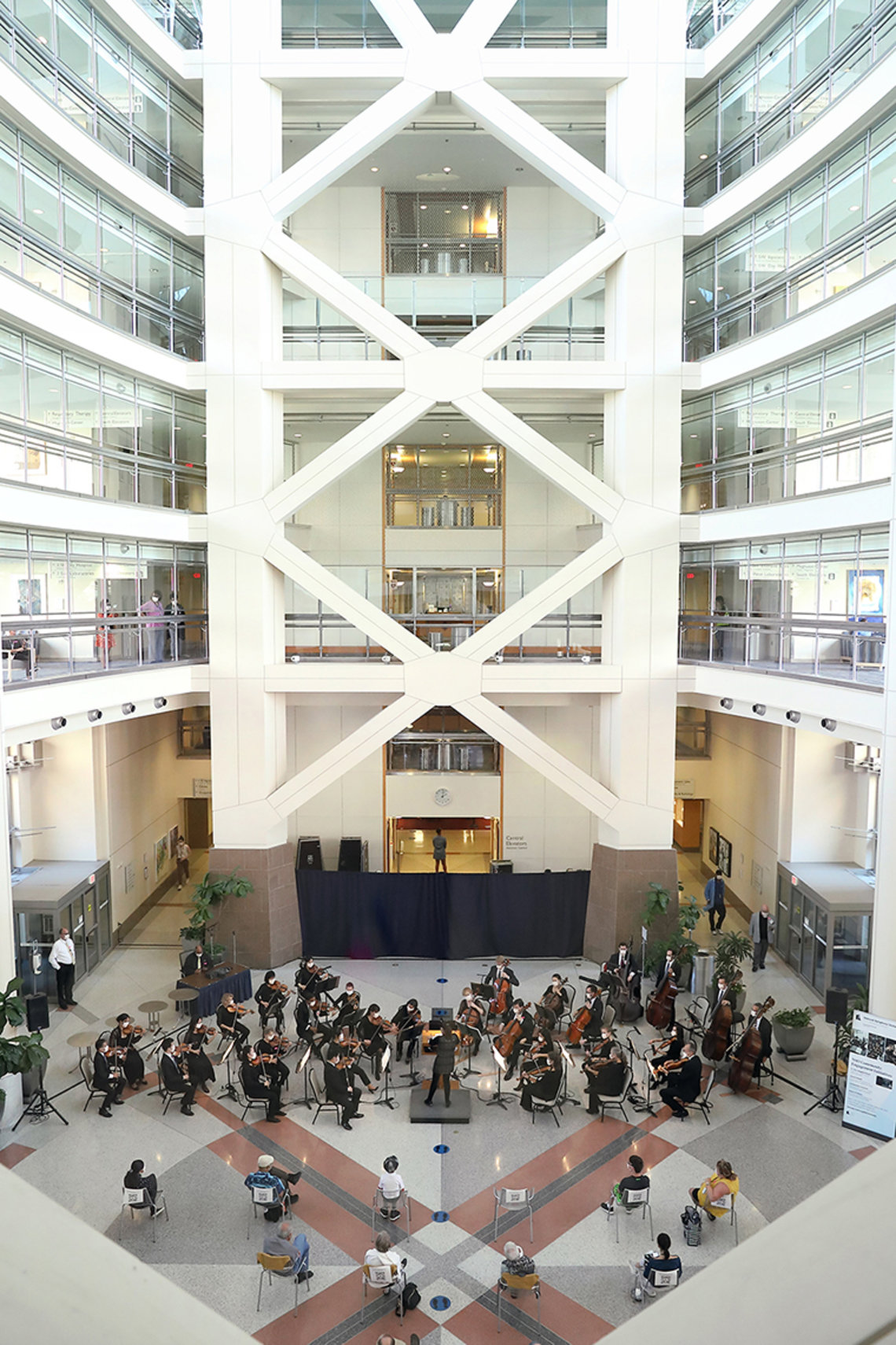 Aerial view of the atrium: orchestra performs with audience scattered, sitting 6 feet apart. Staff can be seen watching through windows in hallways above.