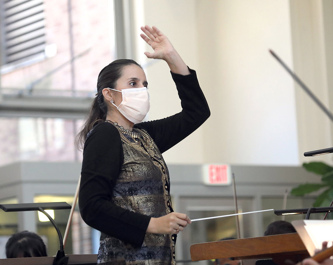 Gonzalez-Granados stands at podium, fingers curled around baton, with other hand raised above her head