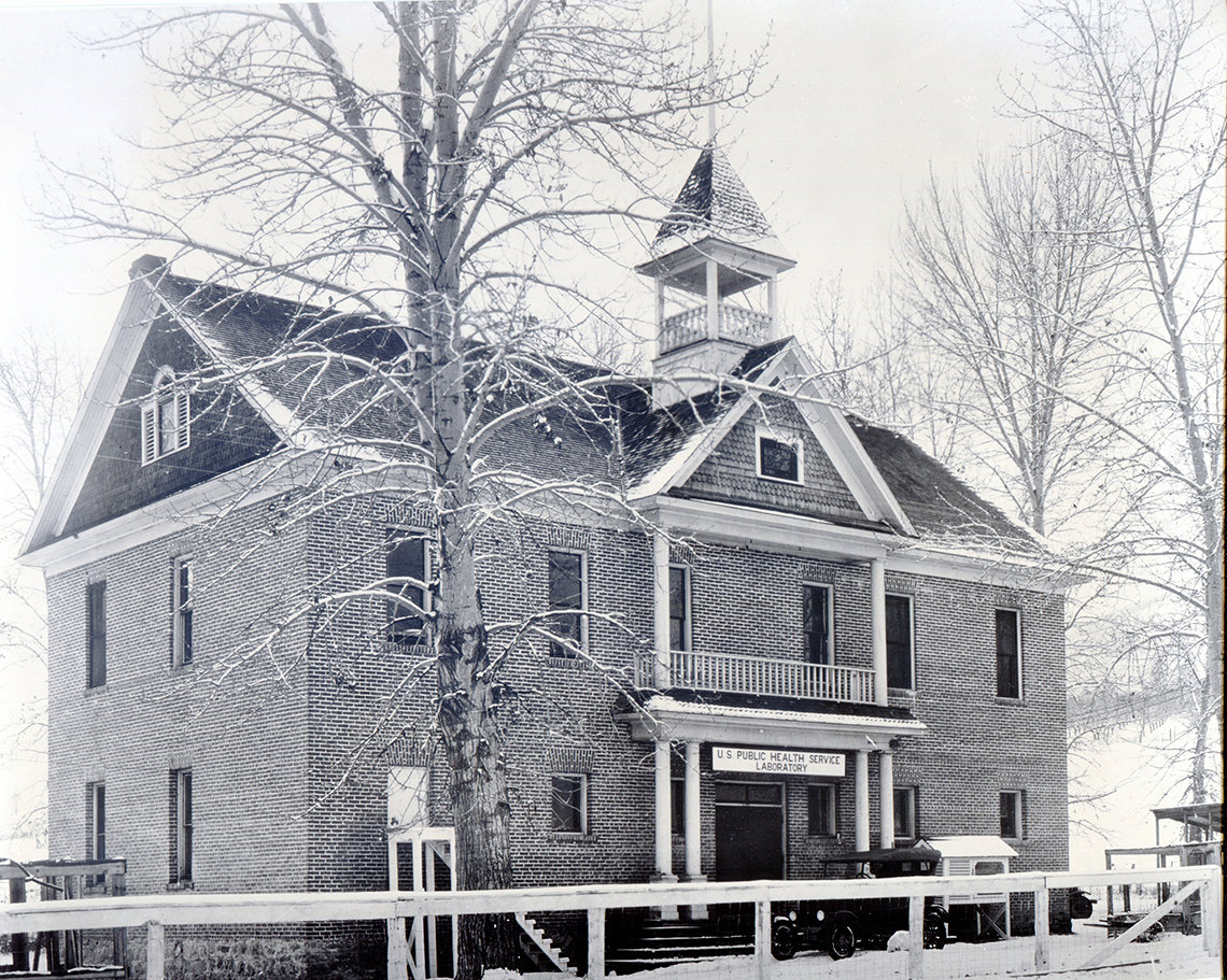 A black and white photograph of a two-story building constructed from locally-made bricks.