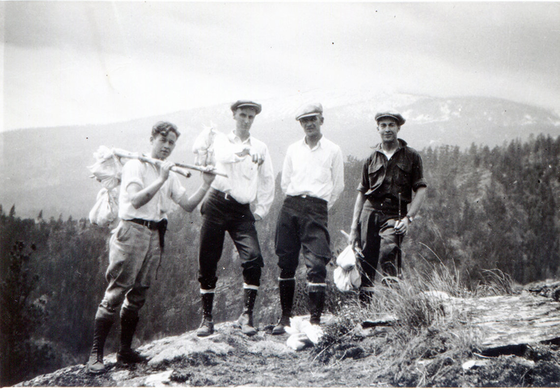 A black and white photo featuring four men holds several white cloth bundles tied to a stick for specimen collection. The background features a large snow covered mountain.