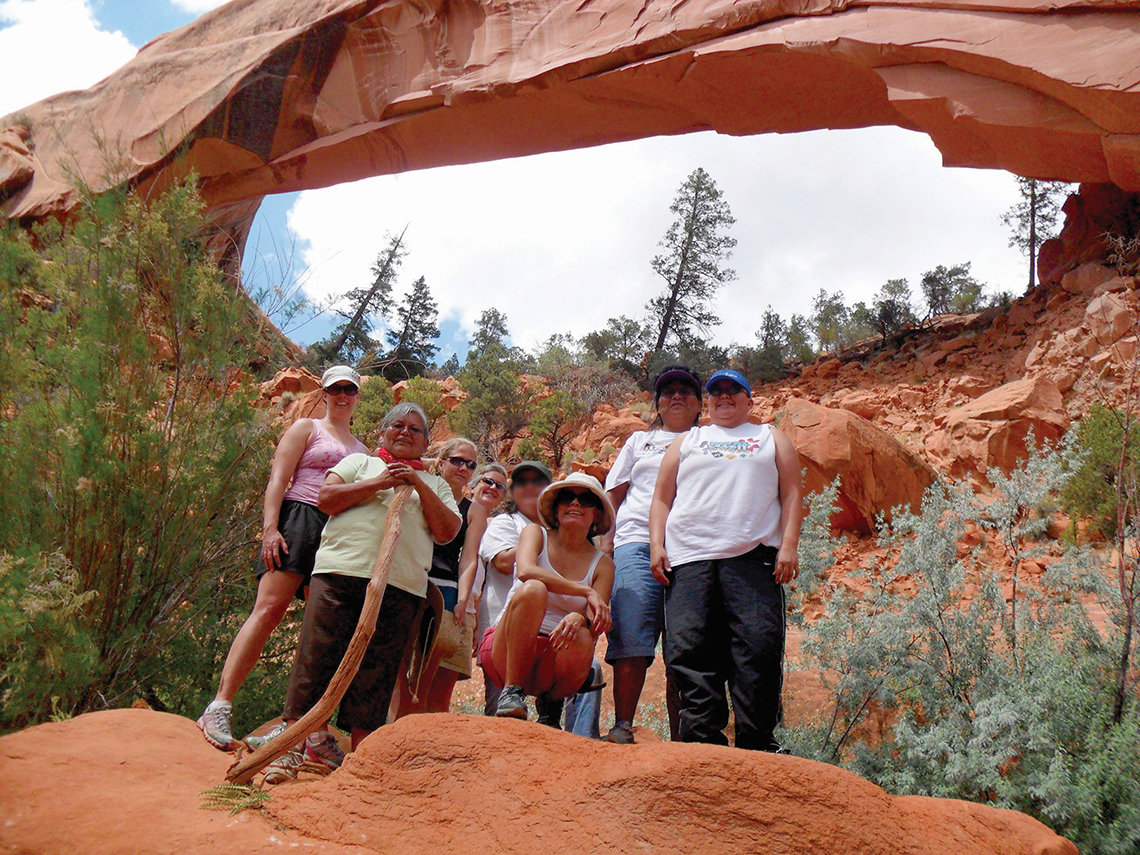 Research team members get a group photo taken below a red stone arch. Pine trees dot the area.