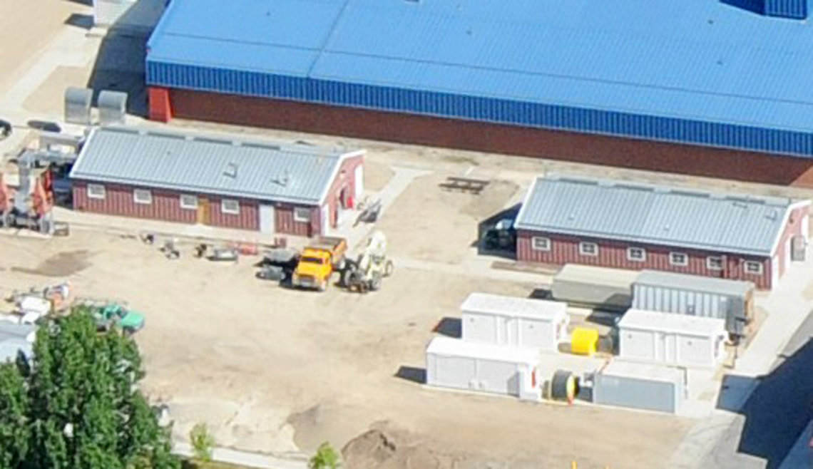 birdseye view of two identical 1-story structures side by side, with several smaller storage units in foreground