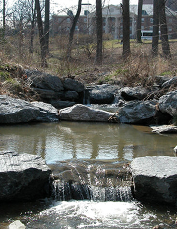 A waterfall flows from a small creek, surrounded by boulders, trees on the NIH campus