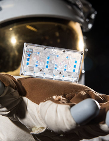 An astronaut in a space suit holds out a small plastic card containing human cells for study.