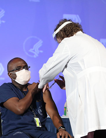 An African American man sits with rolled-up sleeve as a nurse in a white lab coat injects a needle into his arm at the Clinical Center.