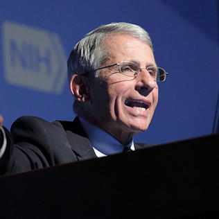 Dr. Fauci talks at podium while pointing a finger