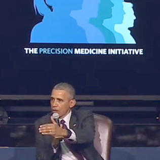 With mic in one hand, Obama gestures with other hand while seated in front of a projected slide.